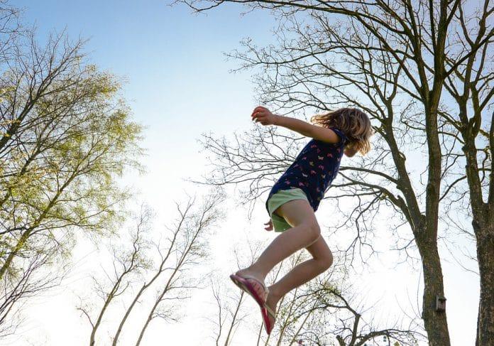 Kindje springt in de lucht met trampoline